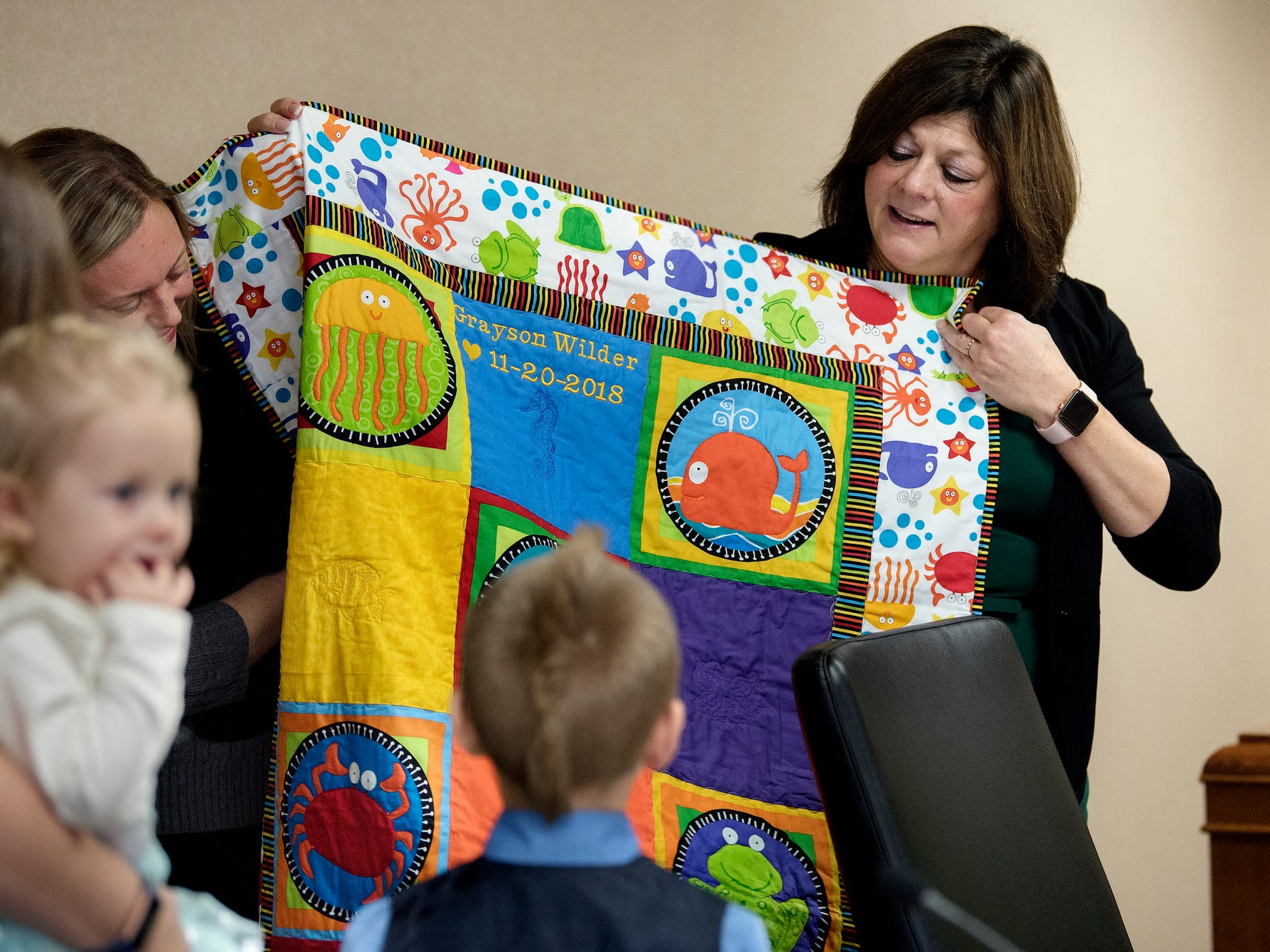 Clinton County Chief Probate Judge Lisa Sullivan, right, and Michigan Supreme Court Justice Elizabeth T. Clement hold up a quilt made for Grayson Wilder, 7, after his adoption was finalized during a Michigan Adoption Day ceremony at the Clinton County Courthouse in St. Johns. Four families finalized the adoptions of six children.