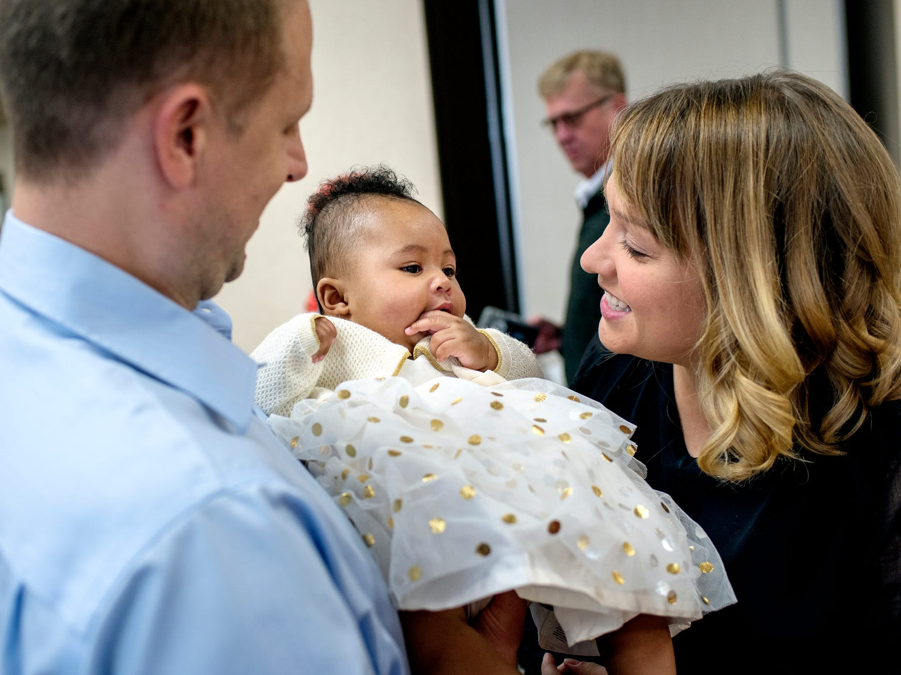Jami Thelen, left, and his wife Erin interact with Ella before the St. Johns couple finalizes the adoption of the five month old during a Michigan Adoption Day ceremony at the Clinton County Courthouse in St. Johns. Four families finalized the adoptions of six children.