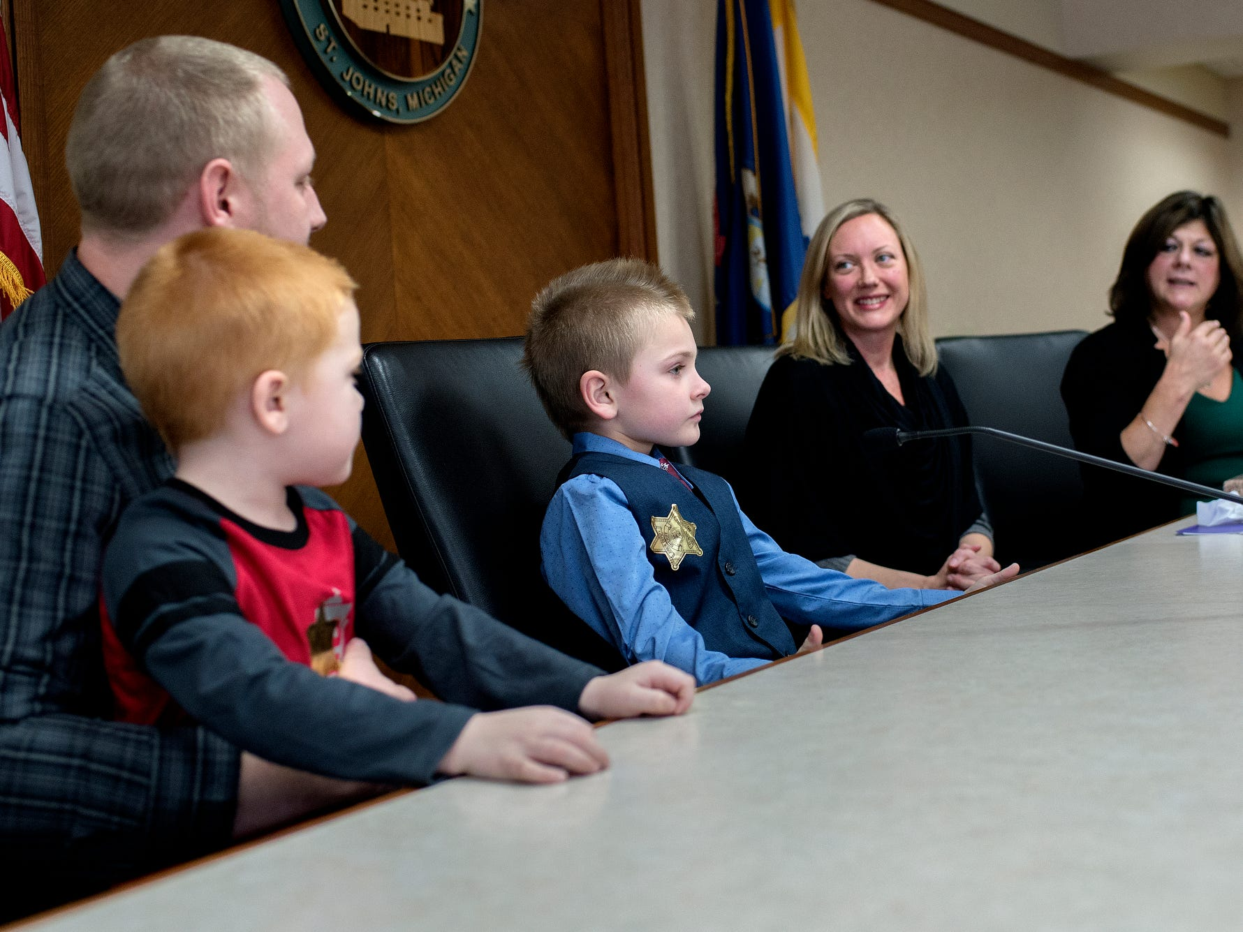 Seven-year-old Grayson Wilder, center, sits at the bench with his family, Michigan Supreme Court Justice Elizabeth T. Clement and Clinton County Chief Probate Judge Lisa Sullivan during Grayson's adoption finalization as part of a Michigan Adoption Day ceremony at the Clinton County Courthouse in St. Johns. Four families finalized the adoptions of six children.