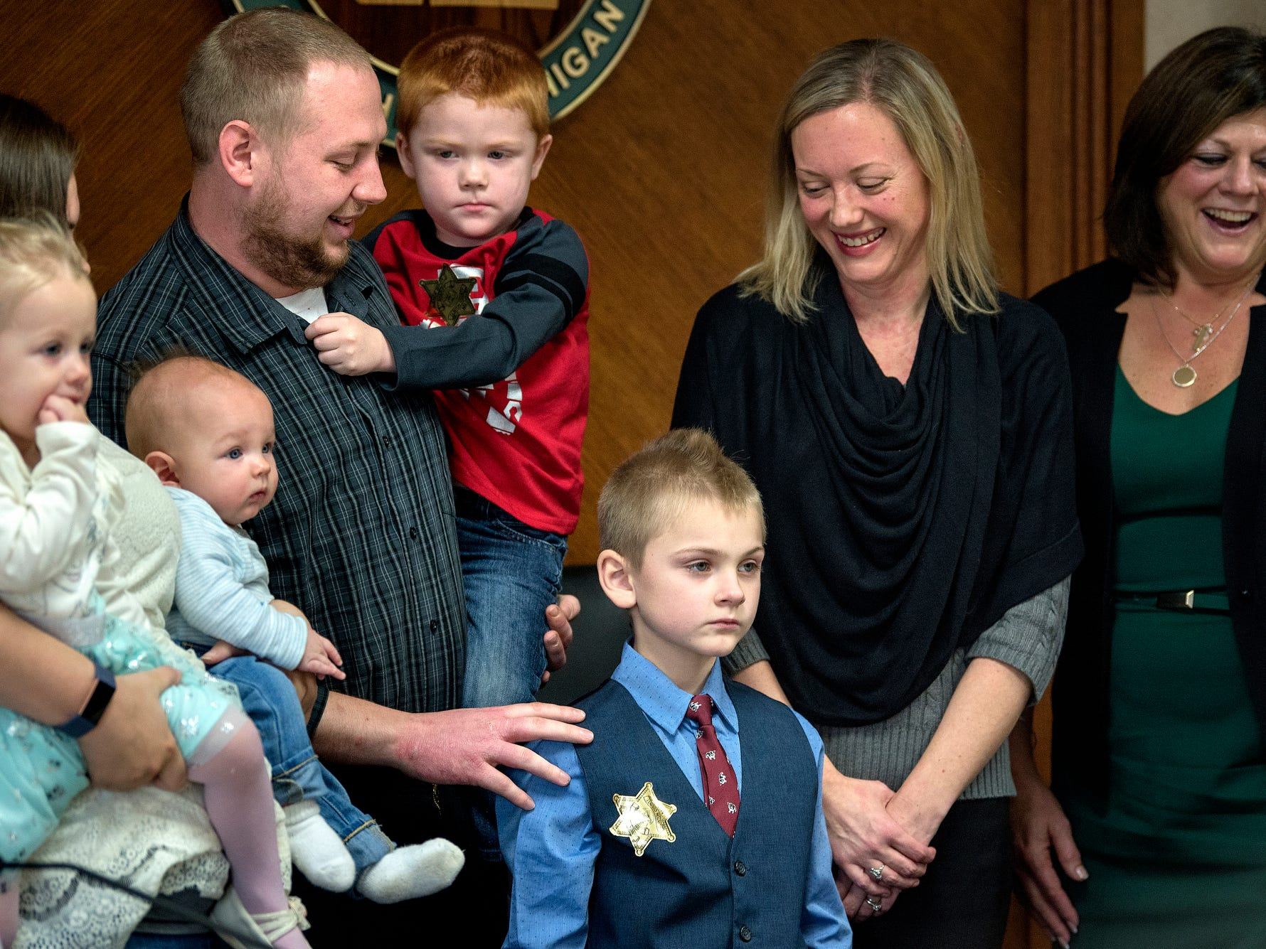Seven-year-old Grayson Wilder, center, stands with his family, left, Michigan Supreme Court Justice Elizabeth T. Clement, second from right, and Clinton County Chief Probate Judge Lisa Sullivan, far right, after Grayson's adoption was finalized during a Michigan Adoption Day ceremony at the Clinton County Courthouse in St. Johns. Four families finalized the adoptions of six children.