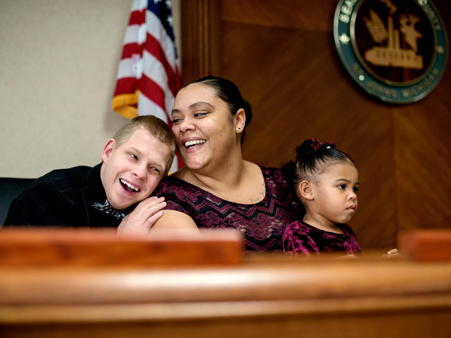 Bath resident Nicole Leggions, center, receives a hug from her adopted brother Paul, left, after Nicole finalized the adoption of Azaria, 3, right, and Aquan, 2, (not pictured) during a Michigan Adoption Day ceremony at the Clinton County Courthouse in St. Johns. Four families finalized the adoptions of six children.