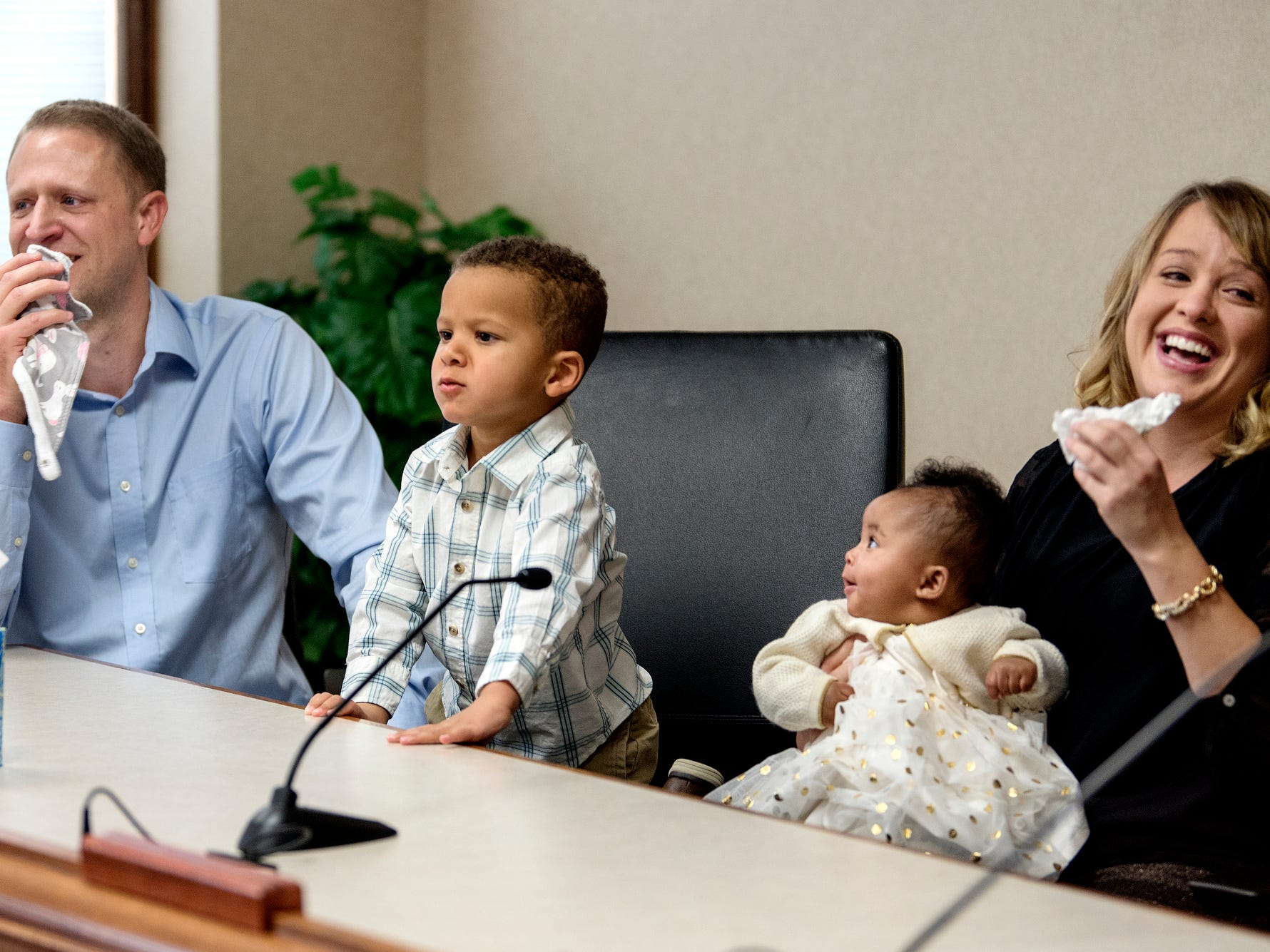 Jami Thelen, left, and his wife Erin, right, laugh as their first adopted son 2-year-old Jaxon, center, hams it up for the crowd during the adoption finalization of 5-month-old Ella at a ceremony inside the Clinton County Courthouse in St. Johns. Four families finalized the adoptions of six children.