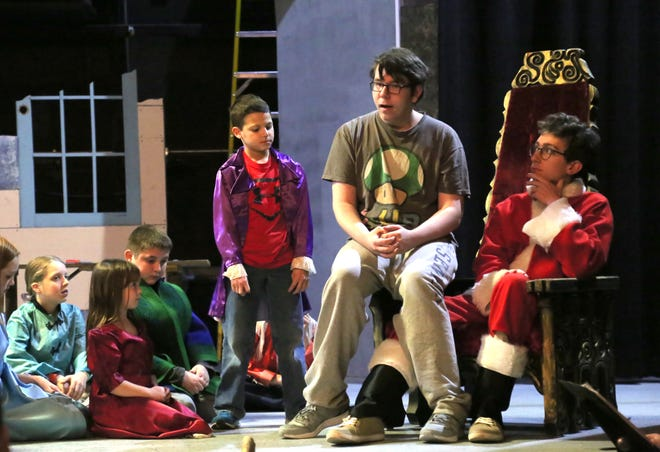 "Joshua Carpenter plays Buddy and Samuel Brands portrays Santa during a rehearsal for the Mansfield Community Playhouse production of ""Elf Jr. """