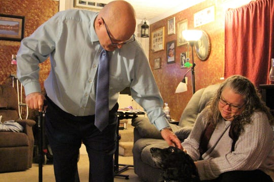 John and Victoria Nagel pet the family dog at their home on South Vine Street. When John first returned home, following an accident that crushed both his hips, he was confined to an electric wheelchair.