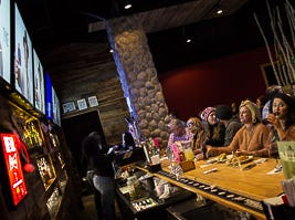 Friends and family sitting at the bar drinking and eating while they wait for Reagan's Strange performance at NBC's Voice at Kooky Canuck in Cordova.