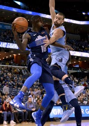 Dallas Mavericks forward Dorian Finney-Smith (10) passes the ball against Memphis Grizzlies center Marc Gasol in the first half of an NBA basketball game Monday, Nov. 19, 2018, in Memphis, Tenn. (AP Photo/Brandon Dill)