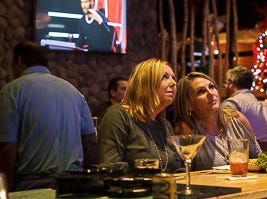 Friends and family sitting at the bar drinking and eating while they wait for Reagan's Strange performance at NBC's Voice at  the watch party at Kooky Canuck in Cordova.