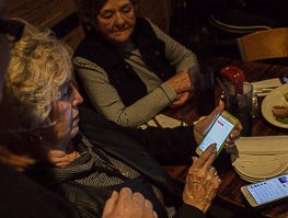 Reagan's Grandmother getting some help with her phone to vote for her grand daughter  during  live on NBC's The Voice watch party for friends and family at Kooky Canuck in Cordova.