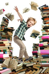 Happy little boy is young reader which is jumping between high piles of books.