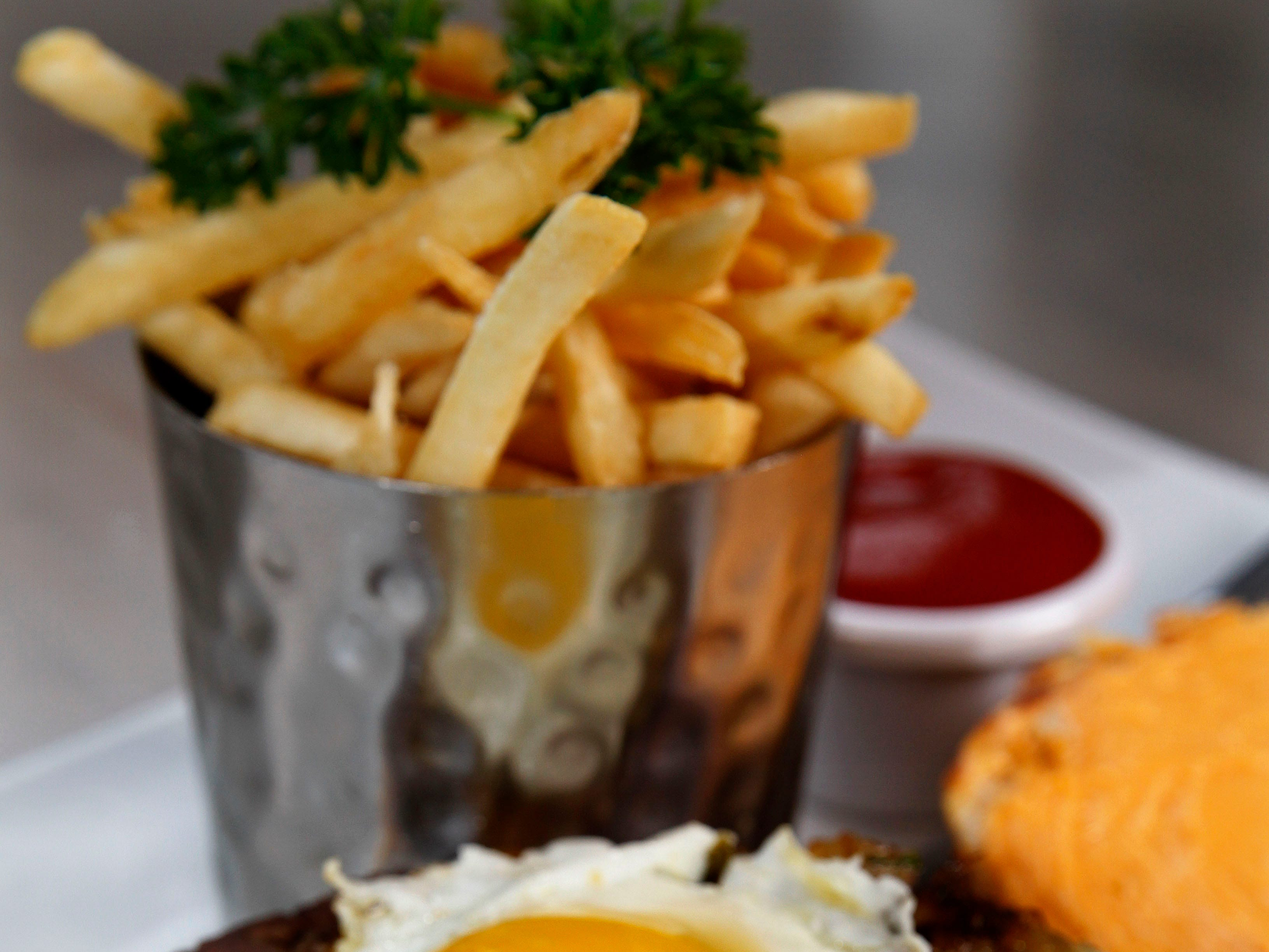 Sweet Diner's breakfast burger is a 1/2-pound Angus beef patty with slices of ham, caramelized onion-jalapeno mix, Merkts cheese and a fried egg, served with fries.
