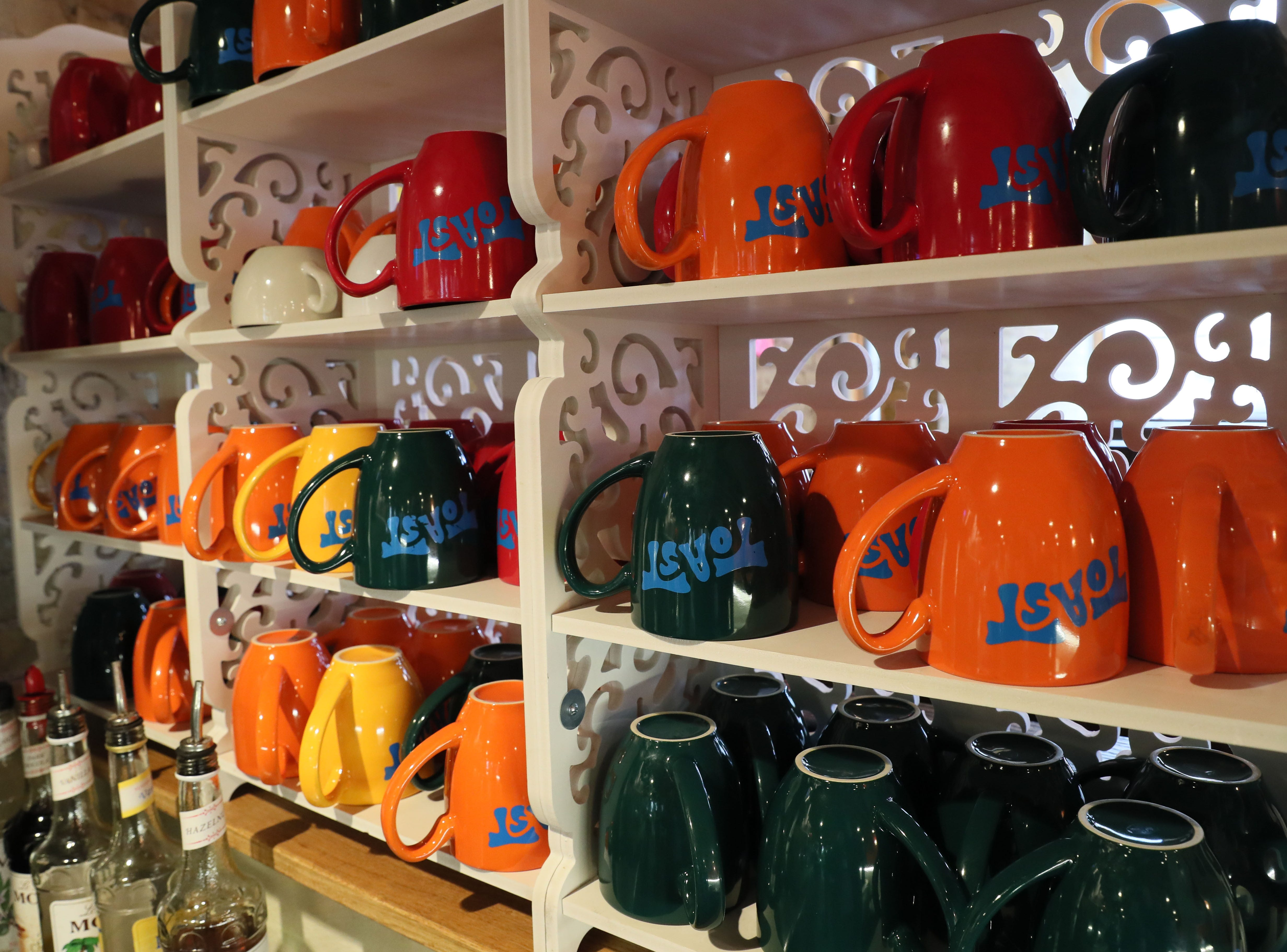 Coffee cups in bright colors fills the racks at Toast.