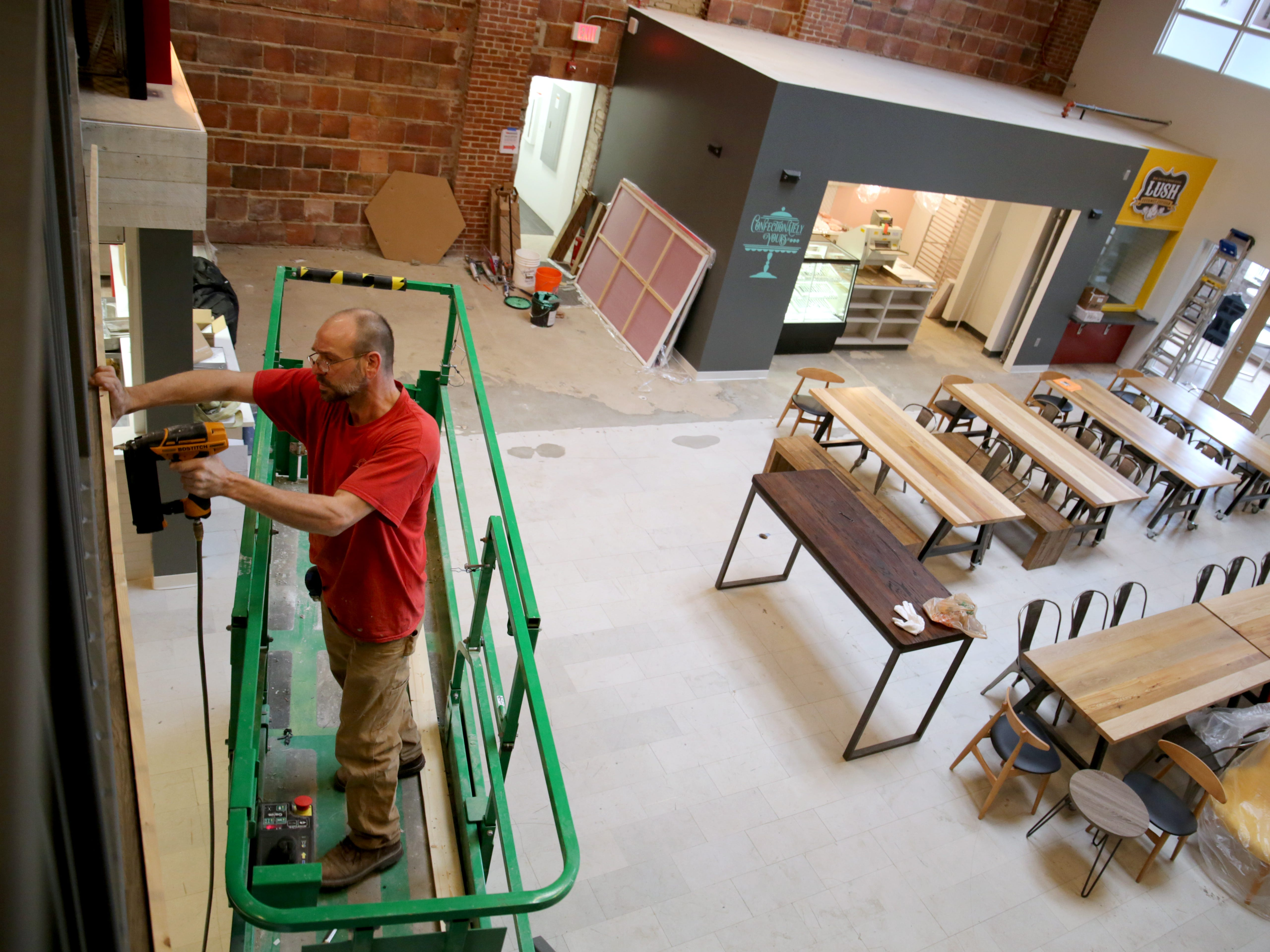 Matthew Sherwood, a carpenter Ogden Construction, works in the large lobby common area on the first floor of Sherman Phoenix that will have seating and several restaurants.