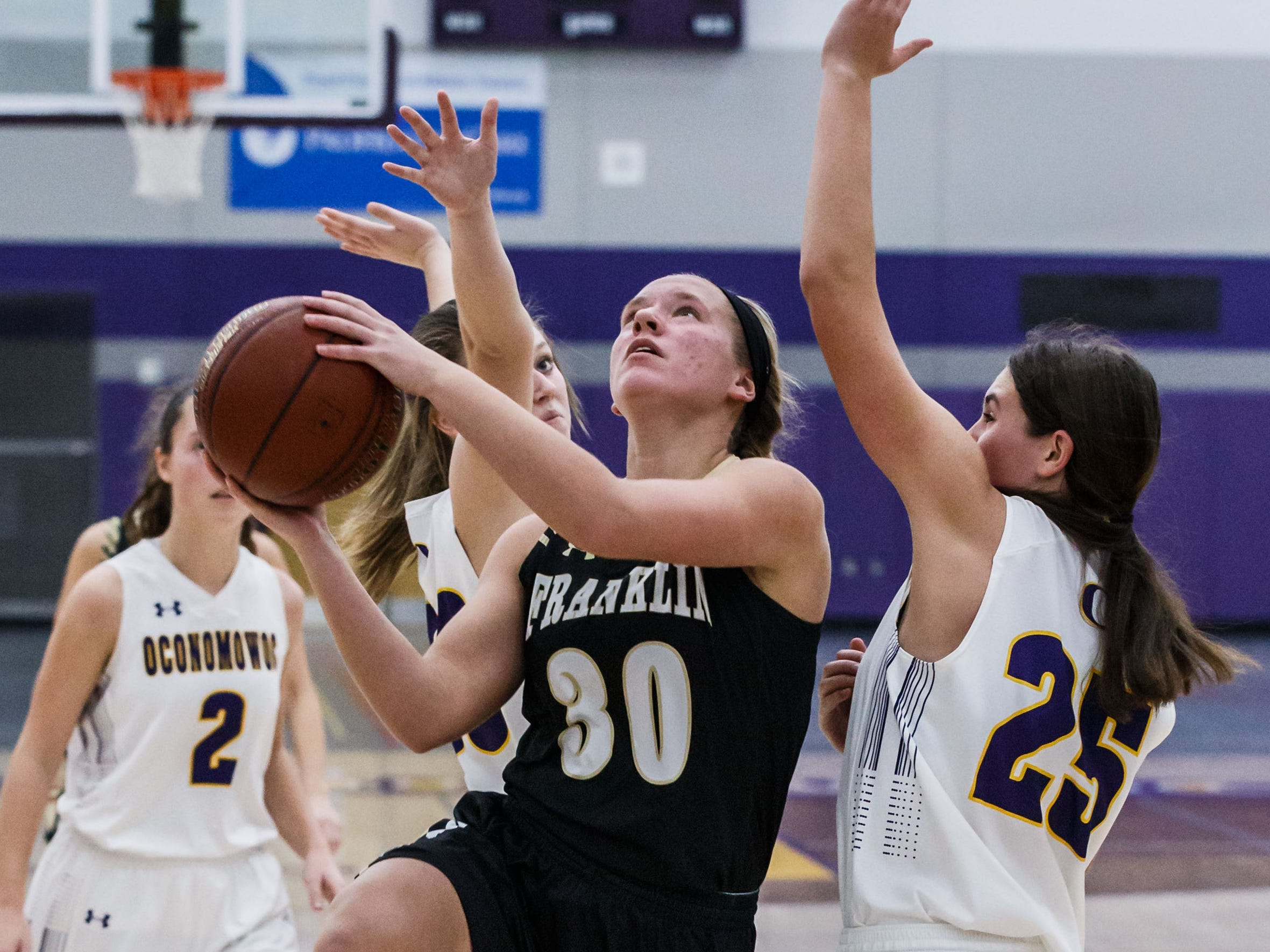 Franklin junior Abigail Matthews (30) drives past defenders during the game at Oconomowoc on Monday, Nov. 19, 2018.