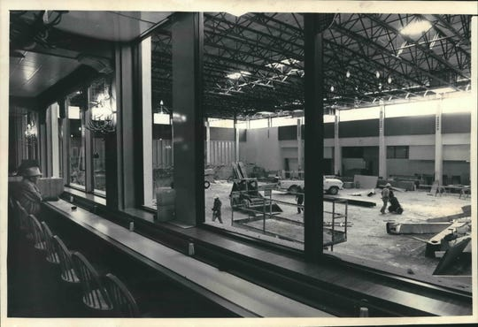 In a photo taken in 1986,  a customer watched from a restaurant at the Mayfair Mall Shopping Center as work continued on the area that once housed the Mayfair Ice Chalet. The rink was removed to accommodate structural changes needed to support a 150,000 - square-foot, second-story addition to the center.