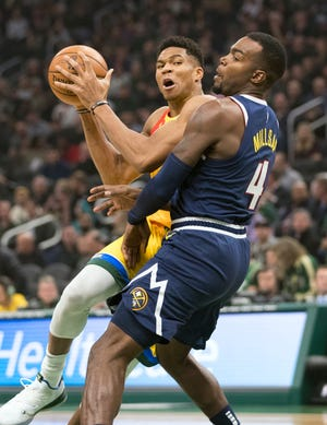 Bucks forward Giannis Antetokounmpo drives to the basket against the Nuggets' Paul Millsap.