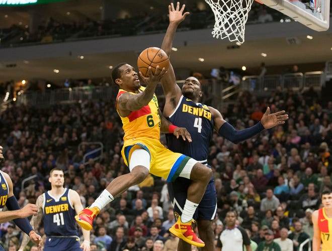Bucks guard Eric Bledsoe gets to the basket and goes up for a shot against Nuggets forward Paul Millsap during the second quarter Monday night.