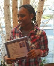 Sandra Parks holds the award she received in the Martin Luther King Jr. Writing Contest.