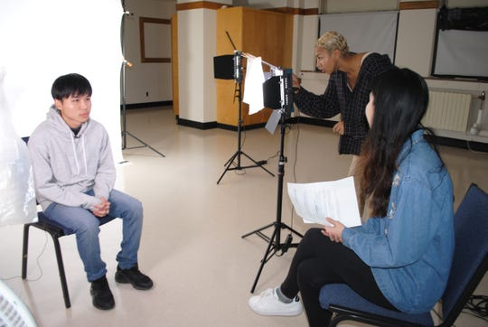 Pulaski High School student Komu Ku (left), who came to the United States from Thailand, sits for a video interview with Minju Kim (right) and Dominica Asberry-Lindquist of Minneapolis-based Green Card Voices.