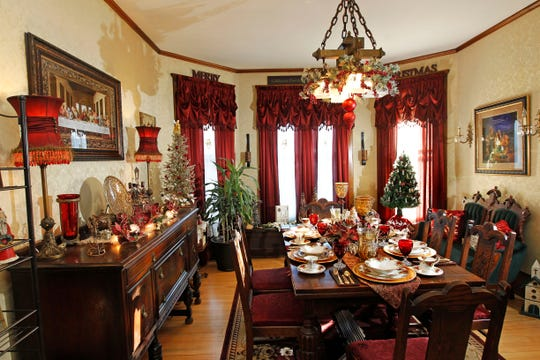 The dining room, with its antique table, buffet and sofa, is decorated for the holiday, even the chandelier.