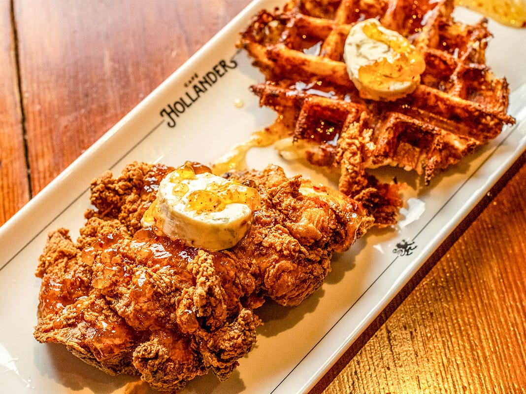 Cafe Hollander serves chicken and waffles, with the waffle made from hash browns; shallot-garlic butter and sparkling wine-honey gastrique accent the dish.