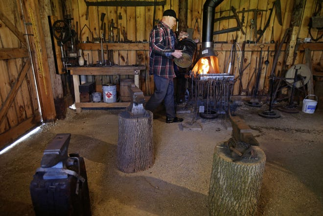 Dave Verboomen tends a fire in the blacksmith shop as the Grignon Mansion in Kaukauna.