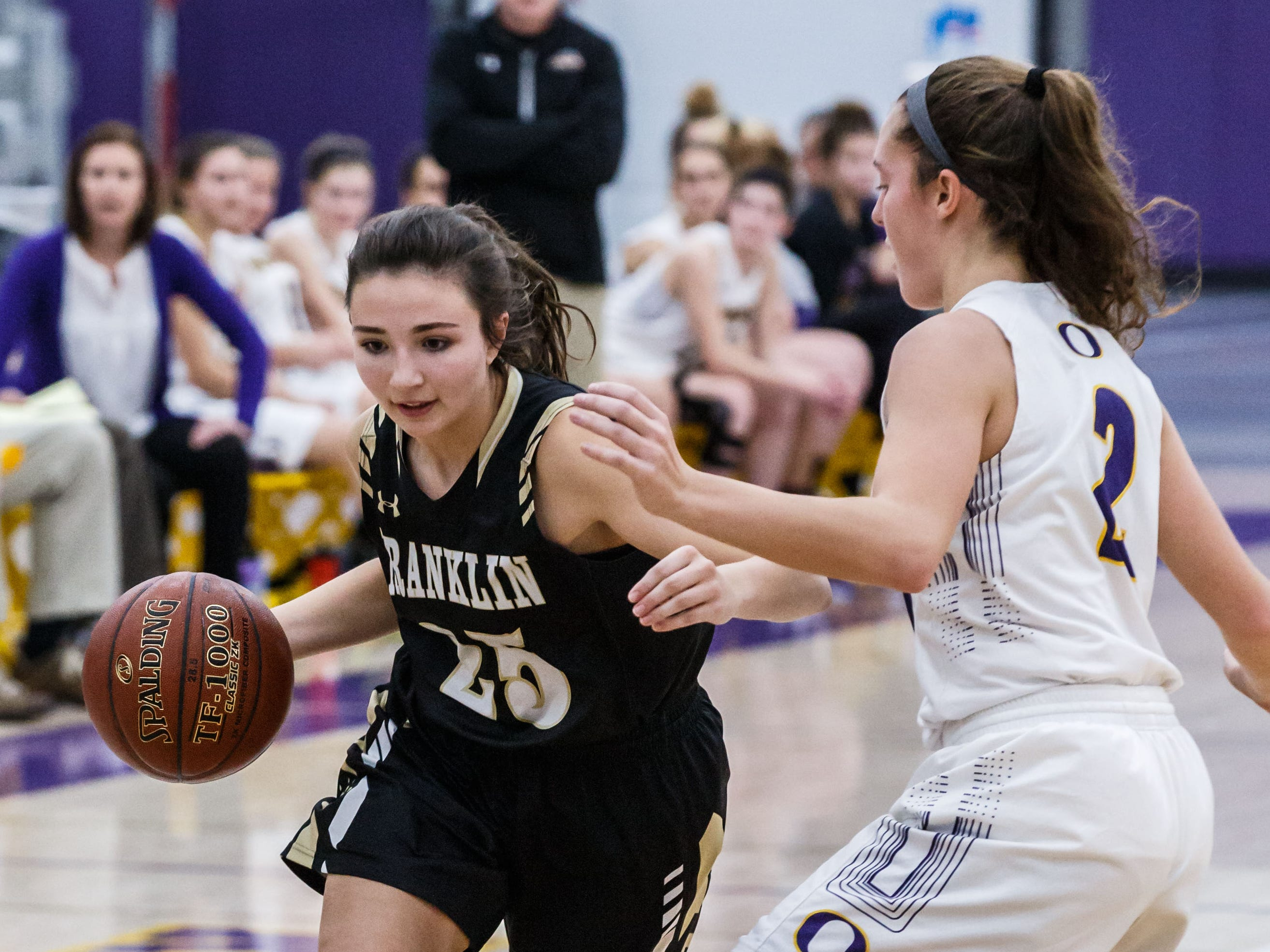 Franklin senior Isabelle Jardas (25) drives past Oconomowoc's Elizabeth Cleary (2) during the game at Oconomowoc on Monday, Nov. 19, 2018.