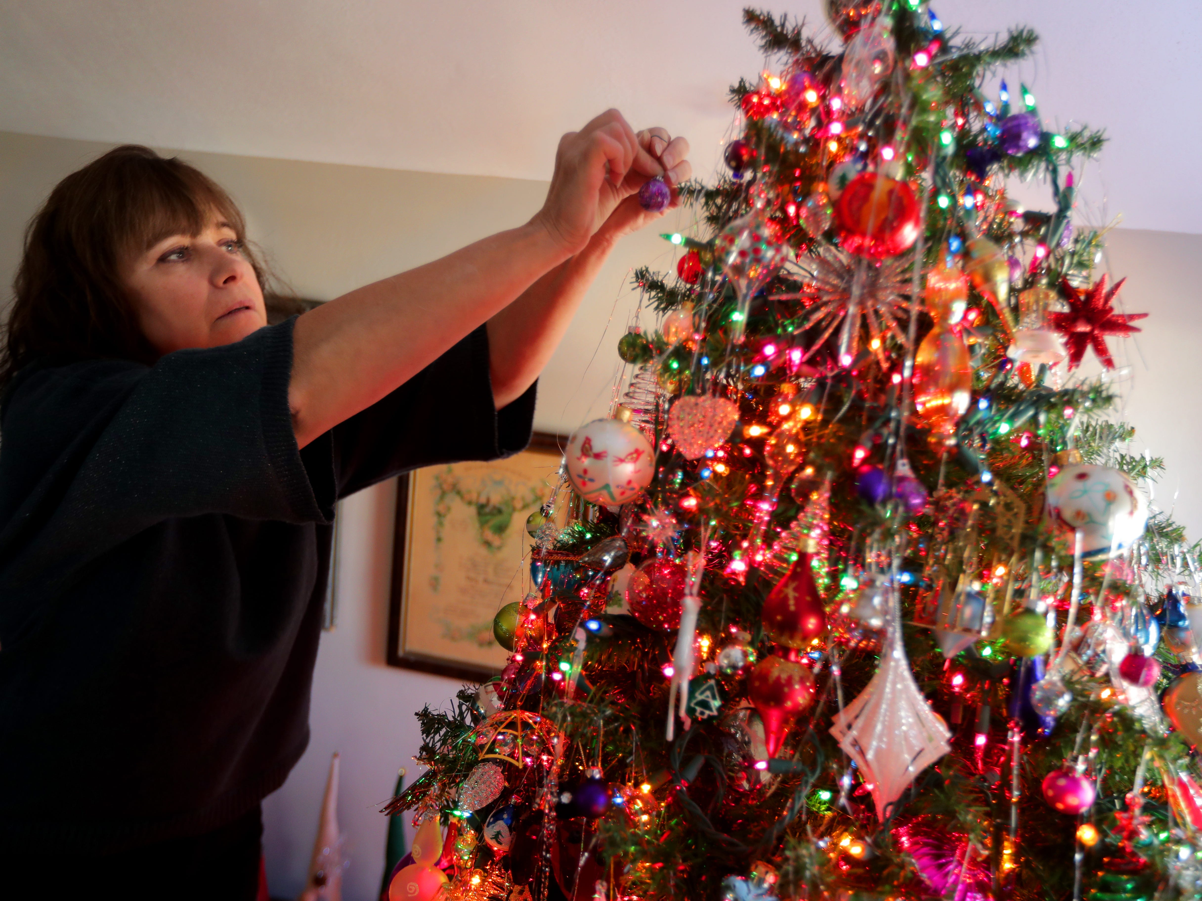 Kim Harrison hangs one more ornament onto her Christmas tree.