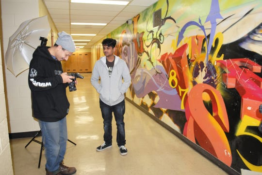 David Buchanan (left), a photographer and videographer with Green Card Voices, checks out the portrait he shot of Pulaski High School sophomore Shaheed Dhaweed as part of a multimedia project showcasing the stories of immigrants in their own words.