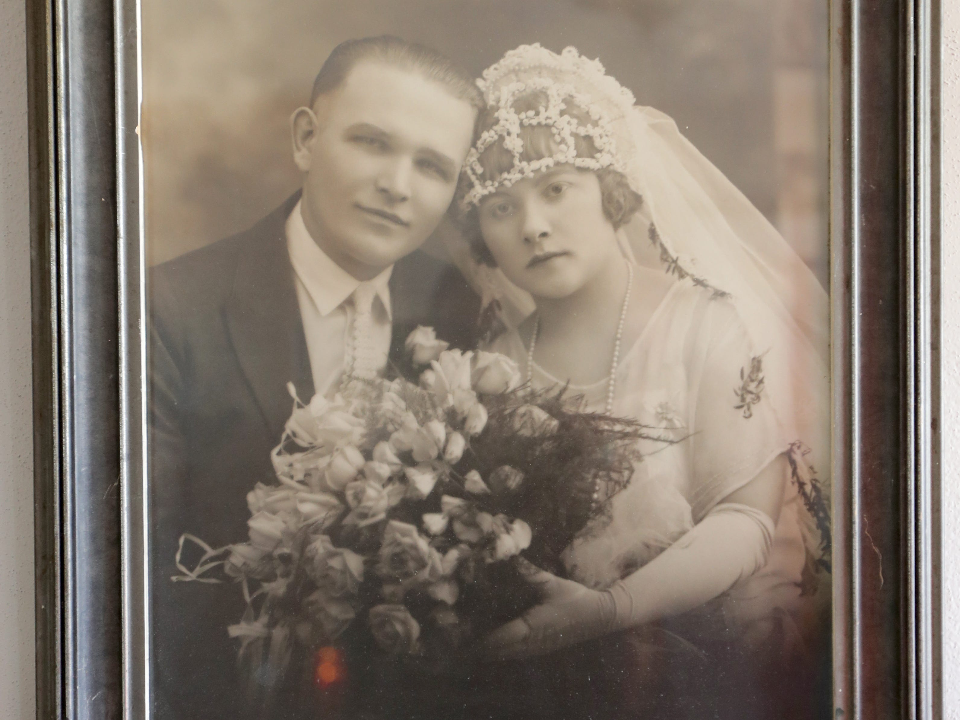 A photo on Kim Harrison's wall shows her grandmother and grandfather on their wedding day in 1925.  Harrison inherited some antique bell Christmas ornaments from her grandmother.