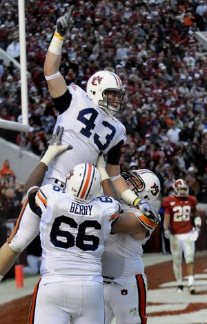 Auburn tight end Philip Lutzenkirchen (43) is lifted in the air by Auburn offensive lineman Mike Berry (66) and Auburn offensive lineman Ryan Pugh (50) after scoring the go-ahead touchdown during second half action in the Iron Bowl at Bryant Denny Stadium in Tuscaloosa, Ala. on Friday November 26, 2010.