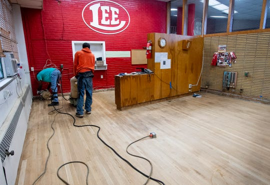 Workers work on the floor in the office at Lee High School in Montgomery, Ala., after pulling out the carpet because of flea infestation on Tuesday November 20, 2018.