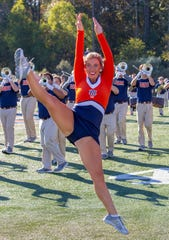 A member of the AUMB dance line keeps her legs straight as she leaps through the air during a morning rehearsal.