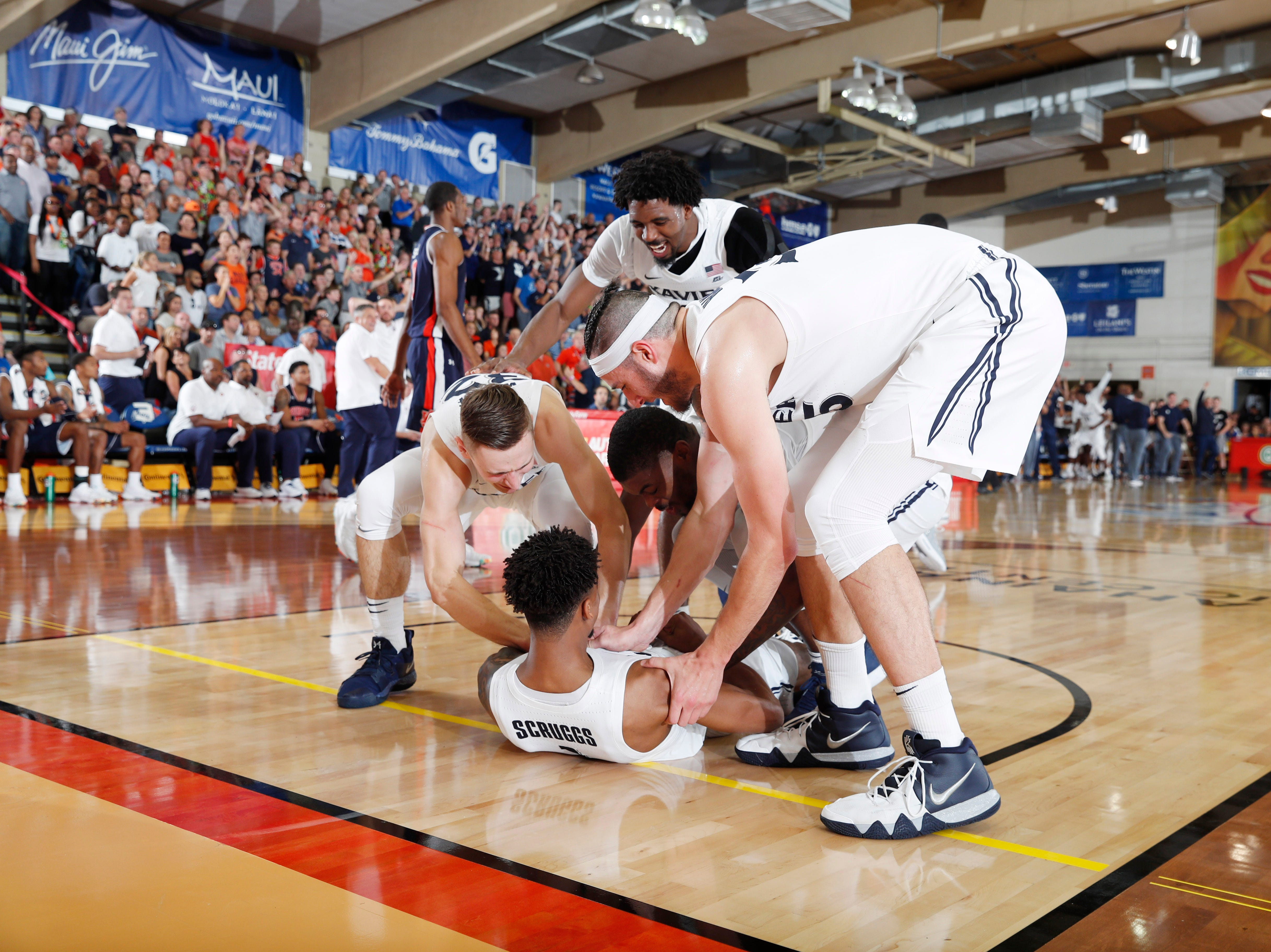 Nov 19, 2018; Lahaina, HI, USA; Xavier Musketeers guard Paul Scruggs (1) is helped off the floor by his teammates  against the Auburn Tigers in the second half during the first round games of the Maui Jim Maui Invitational at Lahaina Civic Center. Mandatory Credit: Brian Spurlock-USA TODAY Sports