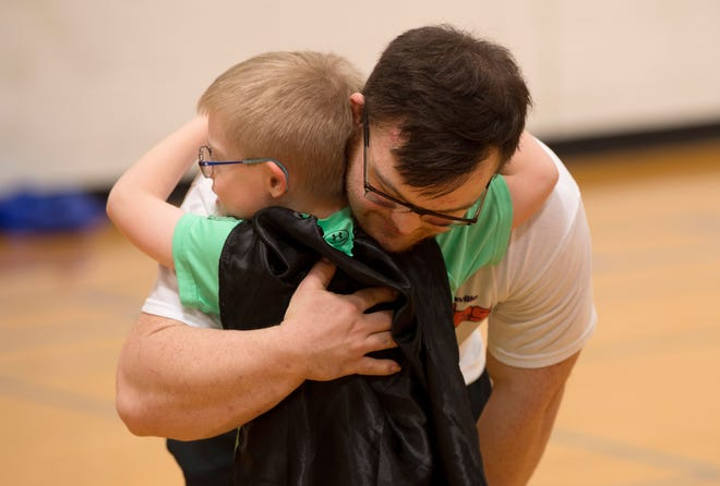 """Calvin Phifer, 6, embraces his role model, Collin Clarke, after the last """"5 for 5"""" exercise class at the University of Evansville in April of 2018. Calvin's mom, Dr. Kate Schwartzkopf-Phifer, is a physical therapist asst. professor at the school and created a workout program with the help of Collin. Calvin also looks to Collin for bodybuilding poses."""