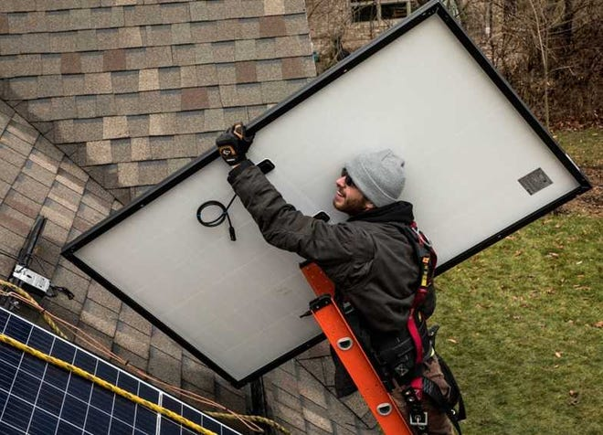 A solar installer climbs the roof of one of more than 40 houses in East Central Indiana that Solarize ECI has helped add solar panels to.