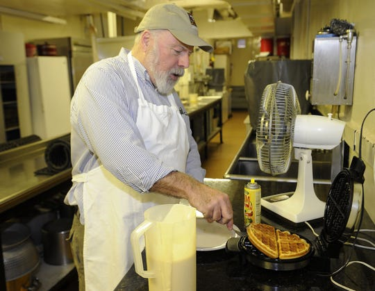 Denny Harris, a member at Downtown Presbyterian Church, separates egg whites as he demonstrates how waffles are made for the Waffle Shop fundraiser at the church Wednesday, Nov. 28, 2012.