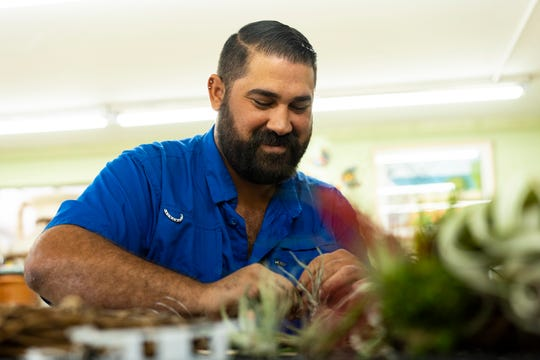 Joel Toledo makes an air plant wreath at the Green Door Nursery in East Naples on Nov. 20, 2018. Toledo said that instead of giving a lecture on how to do something, he wants to be able to give them the experience of creating something hands on. Toledo, offers two type of wreath design, full and asymmetrical. He personally prefers to make an asymmetrical form of wreath over the full.