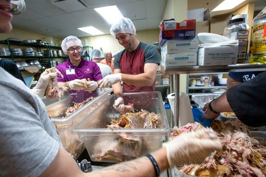 Volunteers Adam Poh, from left, Blake Goucher and Eric Superczinski pull meat off cooked turkeys at New Hope Ministries on Tuesday, Nov. 20, 2018, in East Naples.