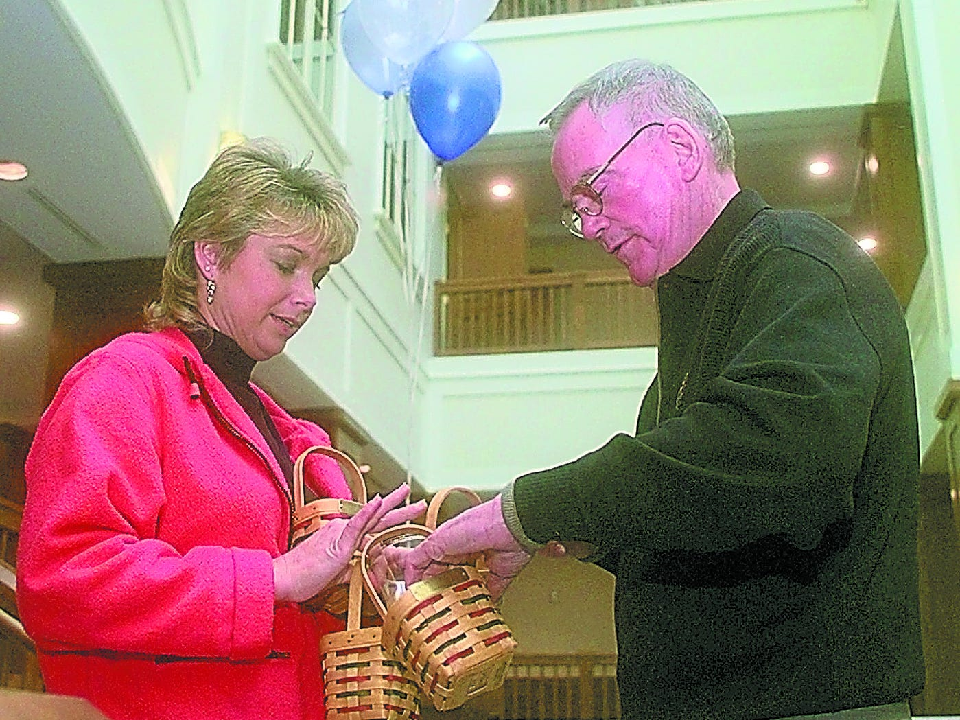 Founder and CEO Dave Longaberger signs a handful of employee holiday baskets for telephone technician Pamela Lutrell, who gathered up baskets from fellow employees to have Dave sign all at once. The Longaberger Company was celebrating the move into their new basket-shaped national headquarters on Wednesday, Dec. 17, 1997.
