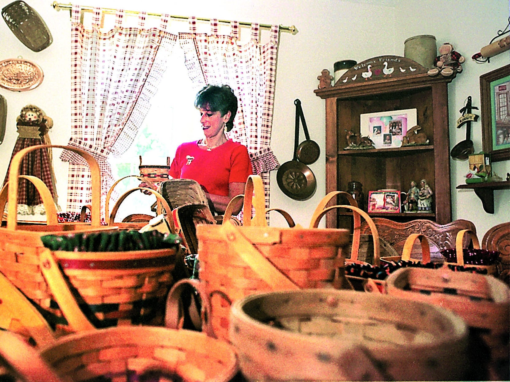 Bonnie Famin holds her smallest Longaberger basket in her Newark home. Famin, who started collecting the baskets in 1974, has no idea how many she owns today.