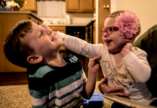 Maci Whisner and her big brother Jake play on the floor of their Heath home in 2018.