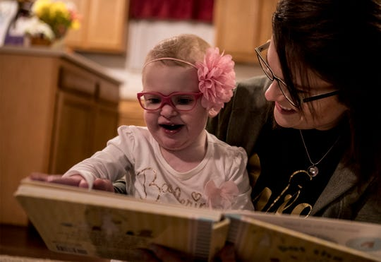 Maci Whisner smiles and laughs as her mom, Karissa, reads a book with her.  Maci who is now two years old has defied the odds. She was born with a heart condition and was placed on hospice are at 1 day old.  After two open heart surgeries, five interventional cardiac catheterizations and many ups and downs, Maci is beginning to live as a regular two year old.