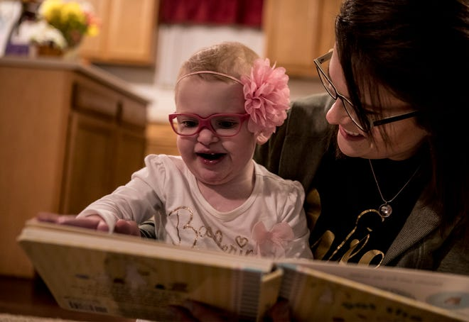 Maci Whisner, then two, smiles and laughs as her mom, Karissa, reads a book with her.  She was born with a heart condition and was placed on hospice are at 1 day old. She passed away on Sept. 19.