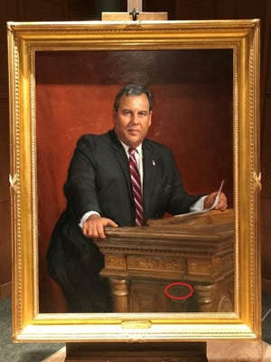 "The letters STTS appear ""etched"" into the side of the lectern on former Gov. Chris Christie's official portrait, unveiled Monday."