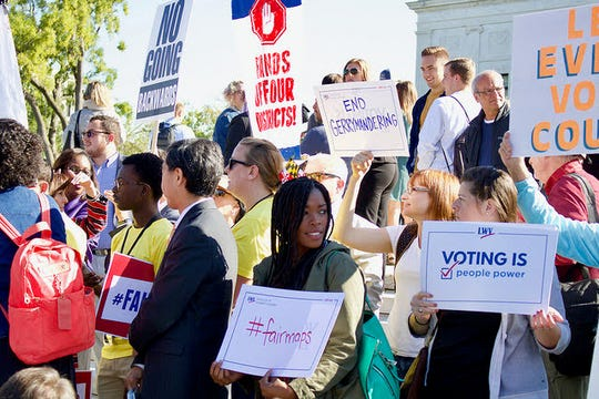 Demonstrators affiliated with the League of Women Voters advocate for redistricting reform and fair maps.