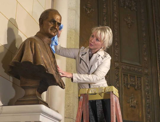 Carolyn Palmer adjusting statue of Pope Paul VI at St. Patrick's Cathedral.