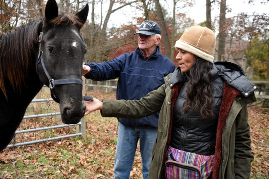Vietnam veteran Kevin Henry, 71 of Allendale and U.S. Marine veteran Amy Steppe greet Hope, a rescued wild American Mustang, now part of the Unbridled Heroes Project family in Allendale. Steppe and her husband U.S. Army veteran Mark Steppe farm the animals at Rohsler's Allendale Nursery. The Steppes' hope to save both the mustangs and returning veterans. Henry is a volunteer with the project, hoping to help ease the transition for younger veterans back to civilian life.