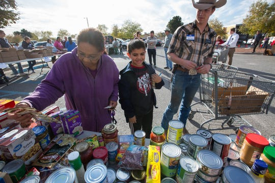 Sarah Lopez, left, with her grandson Nathan Lopez, 9, center, pick up food items from the Roadrunner Food Bank's Mobile Food Pantry , while Austin Reiley a volunteer at the food bank pushes their cart around the parking lot of Peace Lutheran Church, Tuesday November 20, 2018. Everyone that goes through the line gets frozen goods, turkey, fresh vegetables, bread and milk along with a few other items. Much of the  food from the Roadrunner Food bank is rescued food from grocery stories around the state.