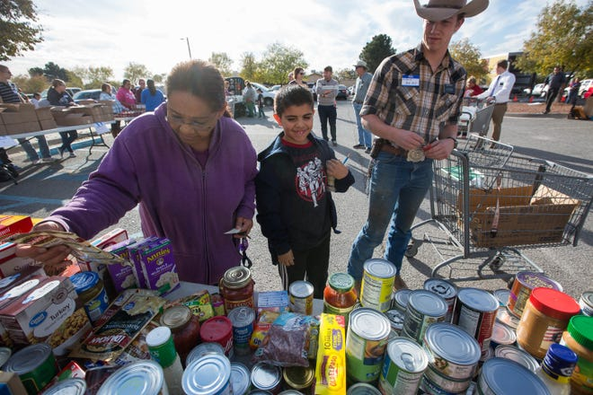 Sarah Lopez, left, with her grandson Nathan Lopez, 9, center, pick up food items from the Roadrunner Food Bank Mobile Food Pantry, while Austin Reiley, a volunteer at the food bank, pushes their cart around the parking lot of Peace Lutheran Church, Tuesday November 20, 2018. Everyone who goes through the line gets frozen goods, turkey, fresh vegetables, bread and milk along with a few other items. Much of the food from the Roadrunner Food Bank is rescued food from grocery stories around the state.