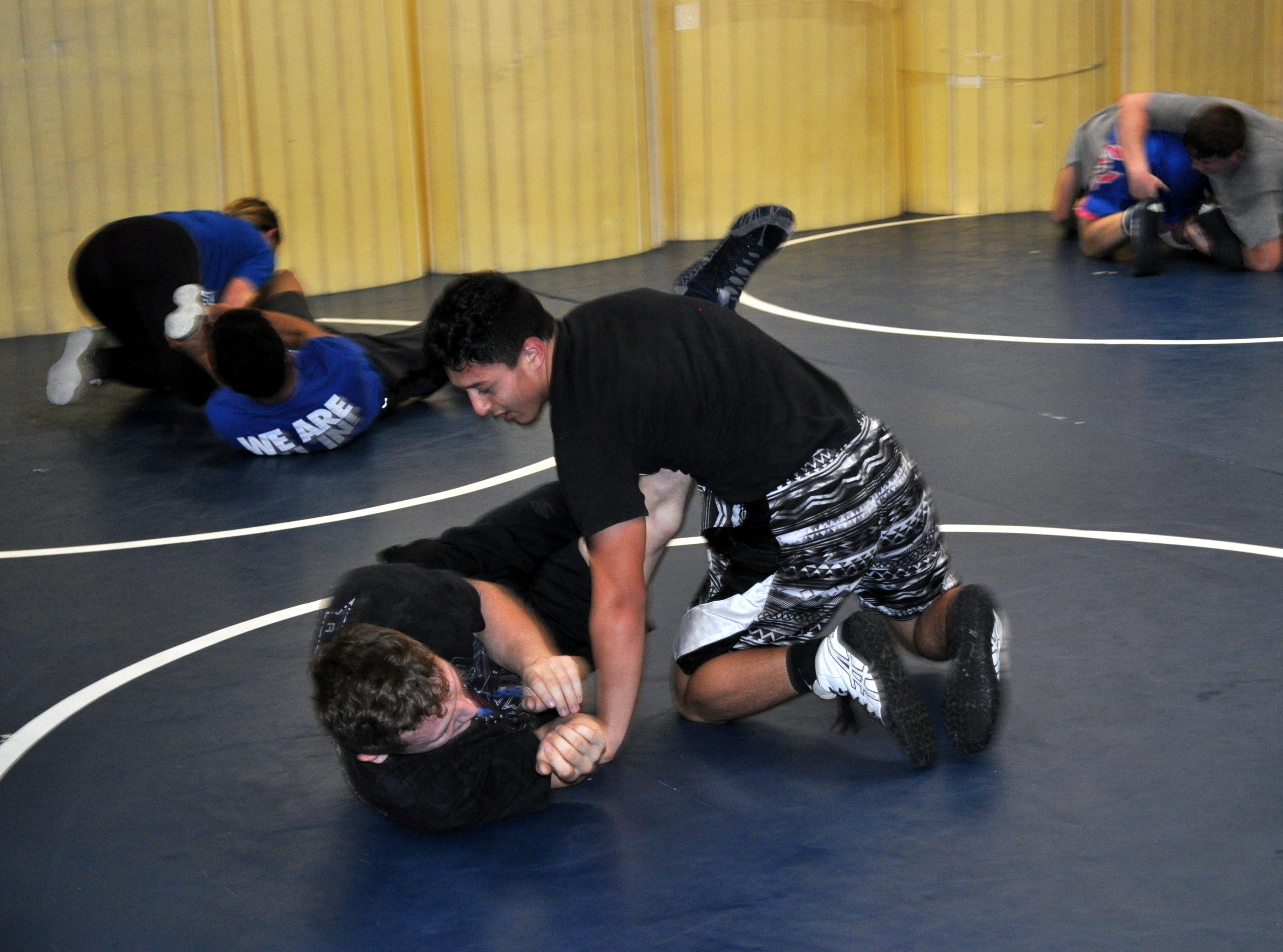 Ivan Villareal (top) and Justin Wood (bottom) get in mat work during Tuesday's practice. Wood finished last year as the state runner-up and is looking for his first title this season.